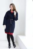 Девушка в пальто представляя на студии Стоковые Фотографии RF