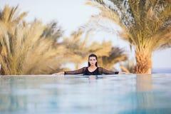 Девушка в пейзажном бассейне на гостинице крыши ослабляет в воде на предпосылке моря и ладоней Стоковая Фотография RF