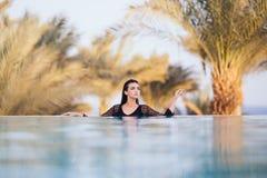 Девушка в пейзажном бассейне на гостинице крыши ослабляет в воде на предпосылке моря и ладоней Стоковые Фотографии RF