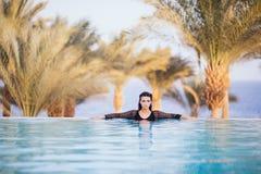 Девушка в пейзажном бассейне на гостинице крыши ослабляет в воде на предпосылке моря и ладоней Стоковые Изображения RF