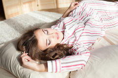 Девушка в пижамах проспала вверх в утре сидит на кровати Стоковая Фотография
