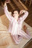 Девушка в пижамах проспала вверх в утре сидит на кровати Стоковая Фотография RF
