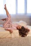 Девушка в пижамах проспала вверх в утре сидит на кровати Стоковое фото RF