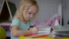 Девушка в питомнике на таблице Младенец рисует в sketchbook В руке на ребенке ручка войлок-подсказки цвета На a акции видеоматериалы