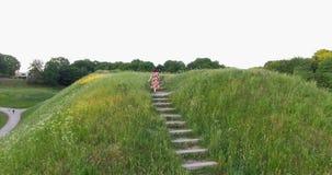 Девушка в платье взбирается вверх деревянные лестницы на горе Воздушная съемка трутня видеоматериал
