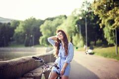 Девушка в платье ехать велосипед через город стоковые фотографии rf