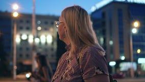 Девушка в платье идя через город вечером Красивые света города видеоматериал