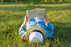Девушка в платье и шляпе лежит на книге чтения зеленой травы над взглядом Стоковые Фото