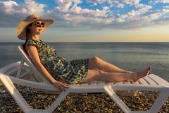 Девушка в платье и шляпе, наслаждаясь заходом солнца лежа на шезлонге стоковая фотография rf