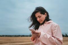 Девушка в плаще Девушка битника портрета осени в пальто использование телефона девушки франтовское Стоковые Фотографии RF
