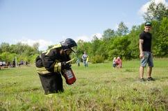 Девушка в пожарном форма подготавливает к тушит горящую автошину на тренировке стоковые фото