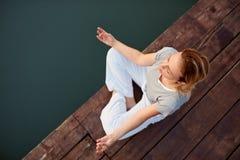 Девушка в положении йоги около воды Стоковое Фото