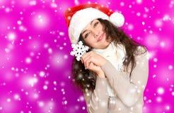 Девушка в портрете шляпы santa при большая игрушка снежинки представляя на розовых предпосылке цвета, концепции праздника рождест Стоковые Фотографии RF