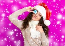 Девушка в портрете шляпы santa при меньшая подарочная коробка представляя на розовых предпосылке цвета, концепции праздника рожде Стоковое фото RF