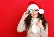 Девушка в портрете шляпы santa при меньшая подарочная коробка представляя на предпосылке красного цвета, концепции праздника рожд Стоковые Изображения RF