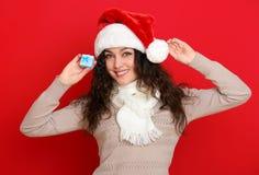 Девушка в портрете шляпы santa при меньшая подарочная коробка представляя на предпосылке красного цвета, концепции праздника рожд Стоковая Фотография