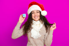 Девушка в портрете шляпы santa при меньшая подарочная коробка представляя на розовых предпосылке цвета, концепции праздника рожде Стоковое Изображение RF