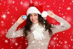 Девушка в портрете шляпы santa при меньшая подарочная коробка представляя на предпосылке красного цвета, концепции праздника рожд Стоковые Фотографии RF