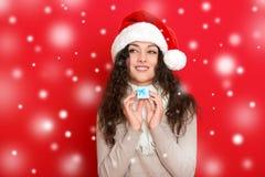 Девушка в портрете шляпы santa при меньшая подарочная коробка представляя на предпосылке красного цвета, концепции праздника рожд Стоковое фото RF