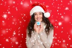 Девушка в портрете шляпы santa при меньшая подарочная коробка представляя на предпосылке красного цвета, концепции праздника рожд Стоковые Фото