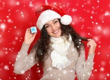 Девушка в портрете шляпы santa при меньшая подарочная коробка представляя на предпосылке красного цвета, концепции праздника рожд Стоковое Изображение RF