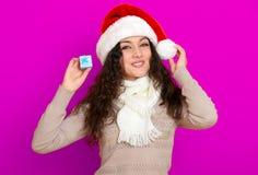 Девушка в портрете шляпы santa при меньшая подарочная коробка представляя на розовых предпосылке цвета, концепции праздника рожде Стоковые Изображения RF