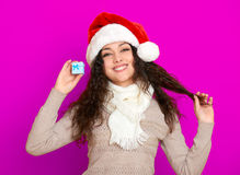 Девушка в портрете шляпы santa при меньшая подарочная коробка представляя на розовых предпосылке цвета, концепции праздника рожде Стоковые Фото