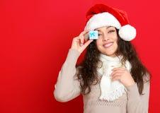 Девушка в портрете шляпы santa при меньшая подарочная коробка представляя на предпосылке красного цвета, концепции праздника рожд Стоковое Фото