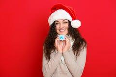 Девушка в портрете шляпы santa при меньшая подарочная коробка представляя на предпосылке красного цвета, концепции праздника рожд Стоковые Изображения
