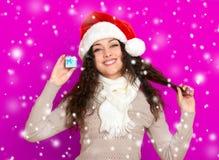 Девушка в портрете шляпы santa при меньшая подарочная коробка представляя на розовых предпосылке цвета, концепции праздника рожде Стоковые Изображения
