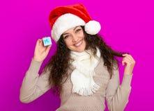 Девушка в портрете шляпы santa при меньшая подарочная коробка представляя на розовых предпосылке цвета, концепции праздника рожде Стоковые Фотографии RF