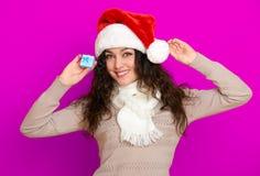 Девушка в портрете шляпы santa при меньшая подарочная коробка представляя на розовых предпосылке цвета, концепции праздника рожде Стоковая Фотография