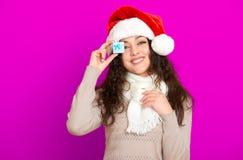 Девушка в портрете шляпы santa при меньшая подарочная коробка представляя на розовых предпосылке цвета, концепции праздника рожде Стоковое Фото