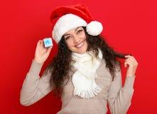 Девушка в портрете шляпы santa при меньшая подарочная коробка представляя на предпосылке красного цвета, концепции праздника рожд Стоковое Изображение