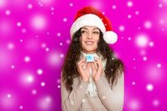 Девушка в портрете шляпы santa при меньшая подарочная коробка представляя на розовых предпосылке цвета, концепции праздника рожде Стоковая Фотография RF