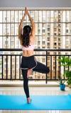 Девушка в представлении йоги дерева дома стоковая фотография