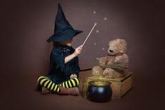 Девушка в произношении по буквам отливки костюма ведьмы на плюшевом медвежонке Стоковое фото RF