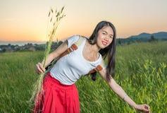 Девушка в пшеничном поле на заходе солнца Стоковая Фотография RF