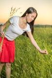 Девушка в пшеничном поле на заходе солнца Стоковое Изображение RF