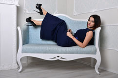 Девушка в платье лежит на голубой софе Стоковая Фотография RF