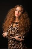 Девушка в платье леопарда и черных ботинках на коричневой предпосылке Стоковые Изображения