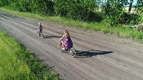 Девушка в платье при ребенок ехать велосипед вдоль полей пшеницы Стрельба с трутнем Красивый ландшафт от a сток-видео