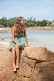 Девушка в платье сидя на утесе морем Стоковое Изображение