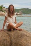 Девушка в платье сидя на утесе морем Стоковое Фото