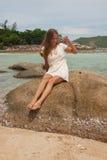 Девушка в платье сидя на утесе морем Стоковая Фотография