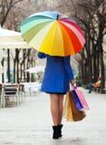 Девушка в плаще с хозяйственными сумками и зонтиком стоковое фото