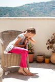 Девушка в плетеном кресле Стоковые Фото