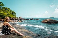 Девушка в пляже утеса на красивом острове (Ilhabela), Бразилии стоковое фото