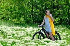 Девушка в древесинах на питьевой воде велосипеда Стоковые Изображения