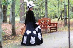 Девушка в ретро XVIII веке платья с valise в парке Стоковое Изображение RF